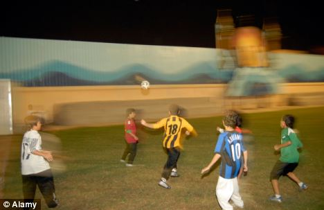 Saudi school children playing football on an artifical pitch in the evening to avoid the heat in Jeddah