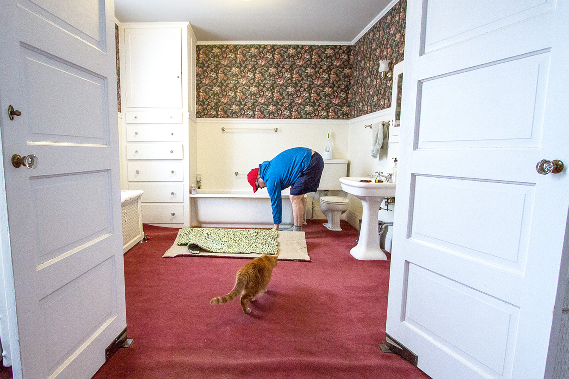 Man removing carpet from a home bathroom