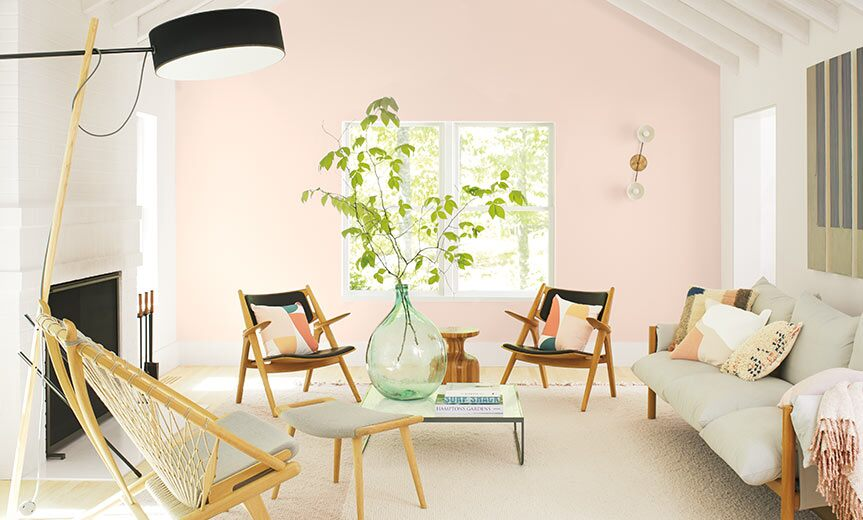 A casual living room with a light pink-painted accent wall