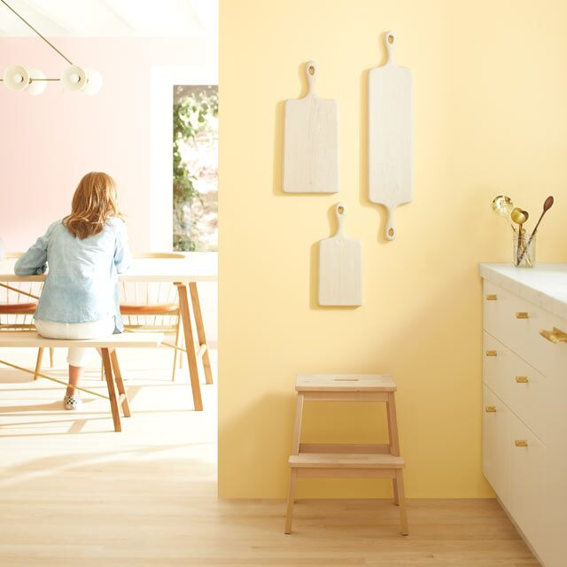 A light kitchen with pale yellow walls and white-painted cabinets